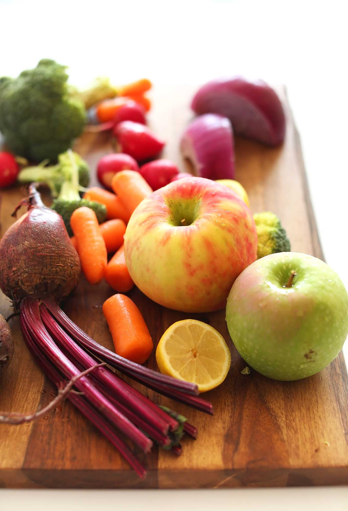 Fresh apples, carrots, beets, broccoli, radish, onions, and lemon for making a healthy fall slaw