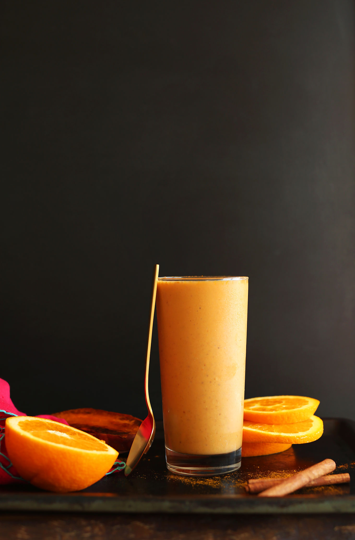 Spoon resting on a glass filled with our Creamy Sweet Potato Smoothie recipe