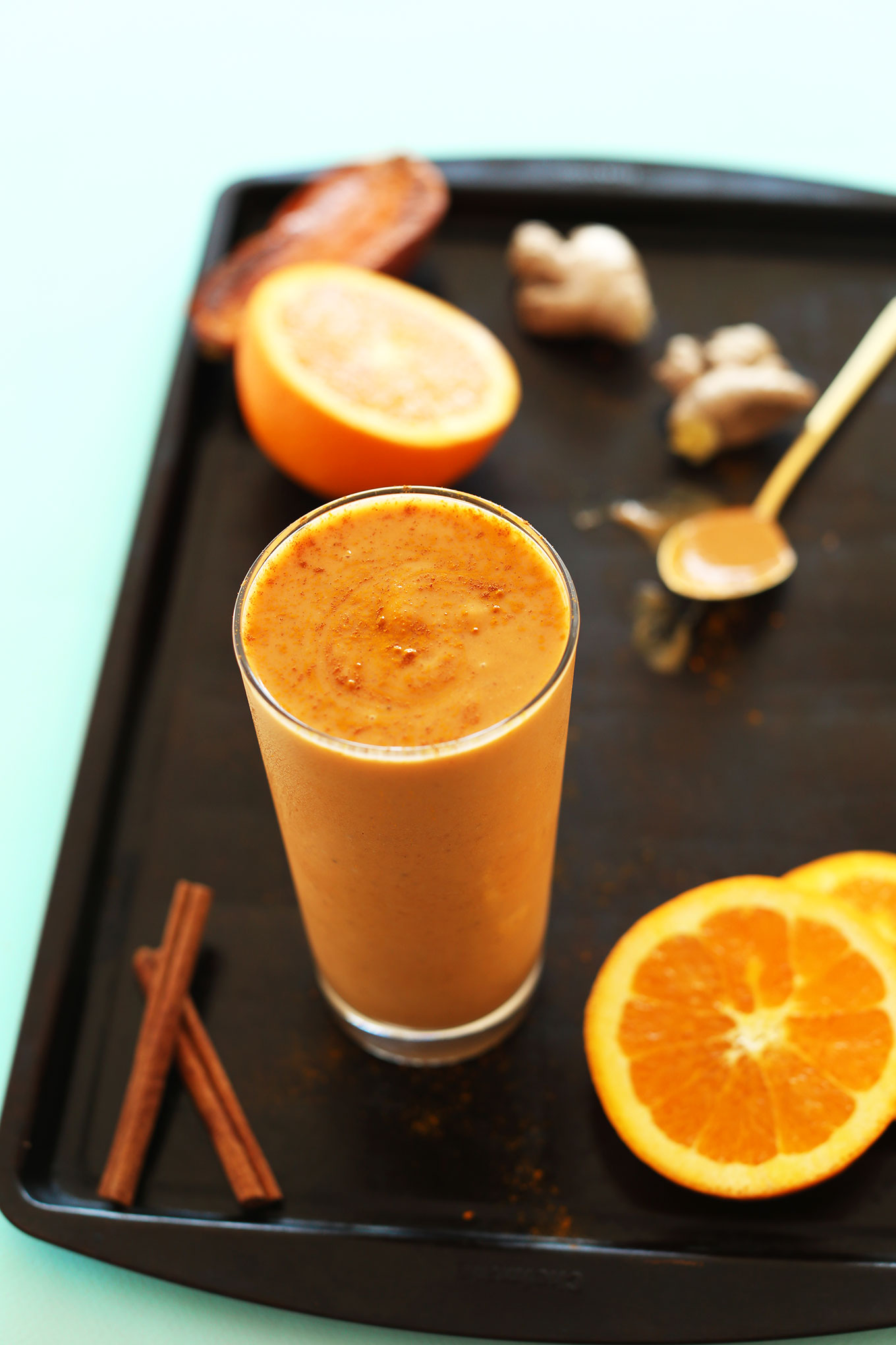Glass of our Creamy vegan Sweet Potato Smoothie with oranges, cinnamon, and ginger