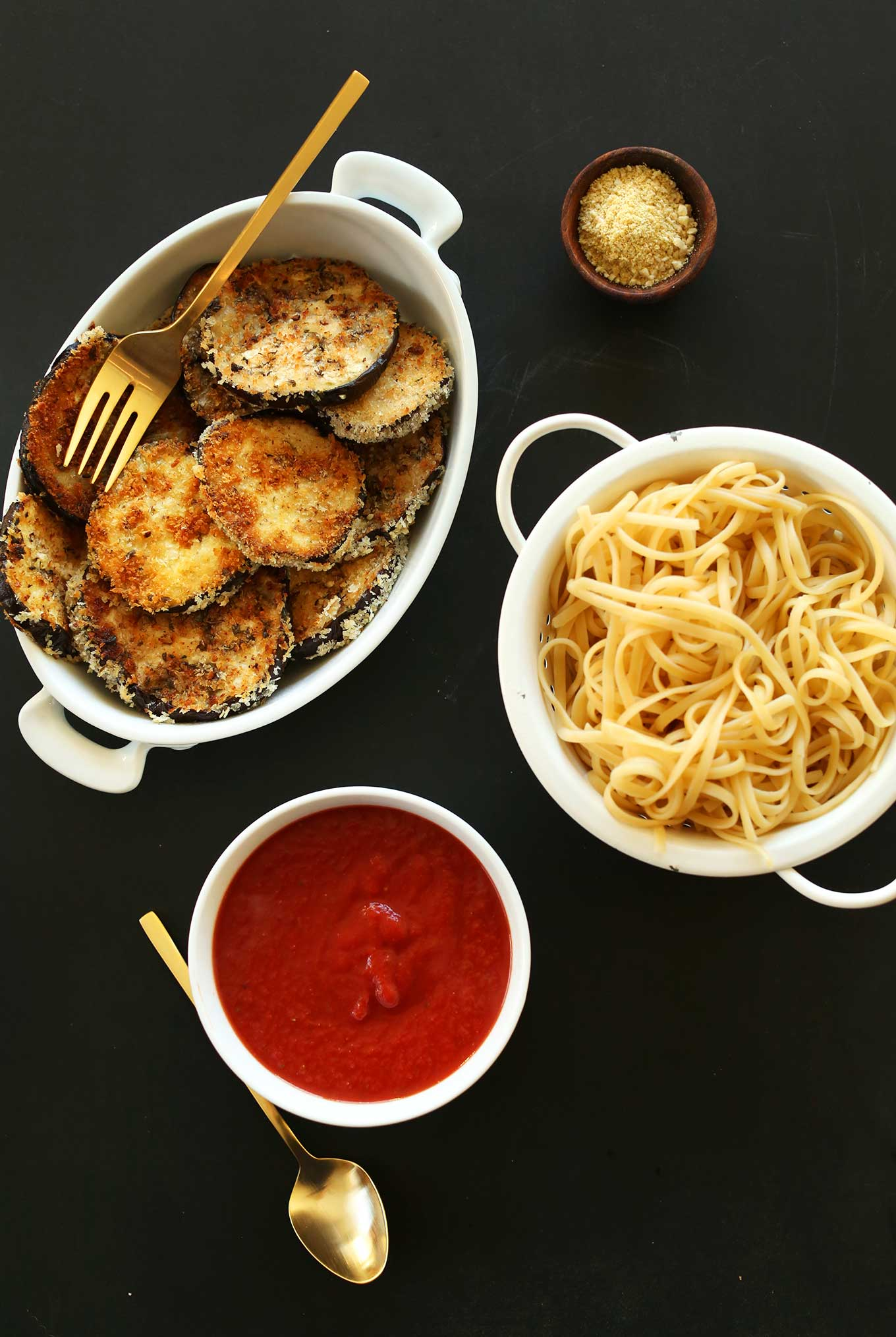 Dishes of marinara, pasta, vegan parmesan, and vegan eggplant parmesan for a comforting meal