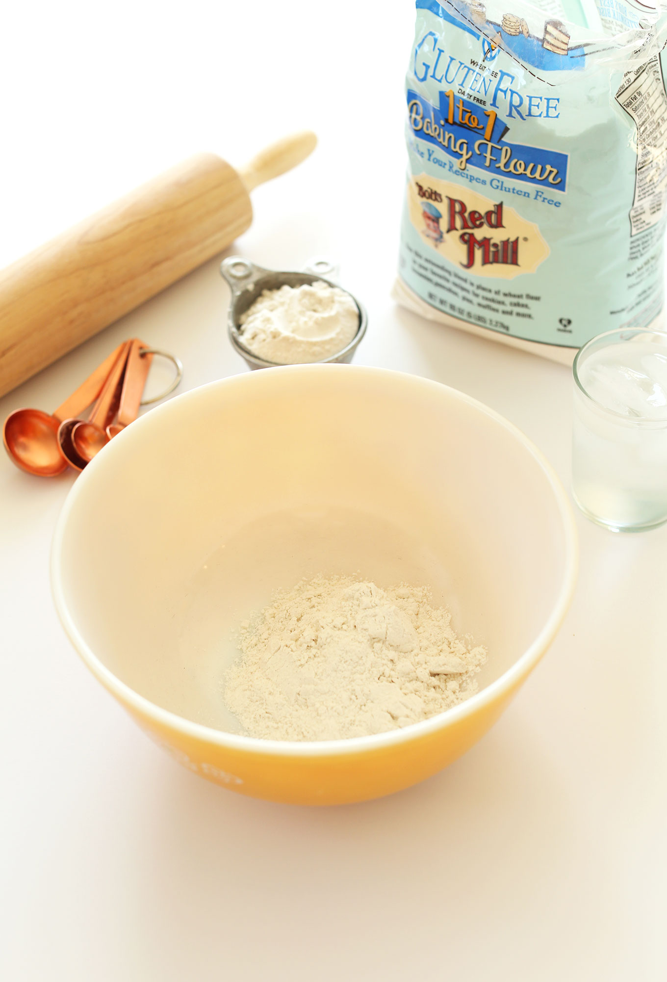 Bowl and measuring cup of Bob's Red Mill Gluten-Free Baking Flour next to a rolling pin and measuring spoons