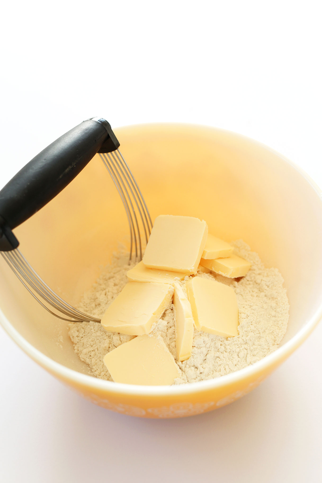 Pastry cutter to in a bowl with gluten-free flour and slices of vegan butter
