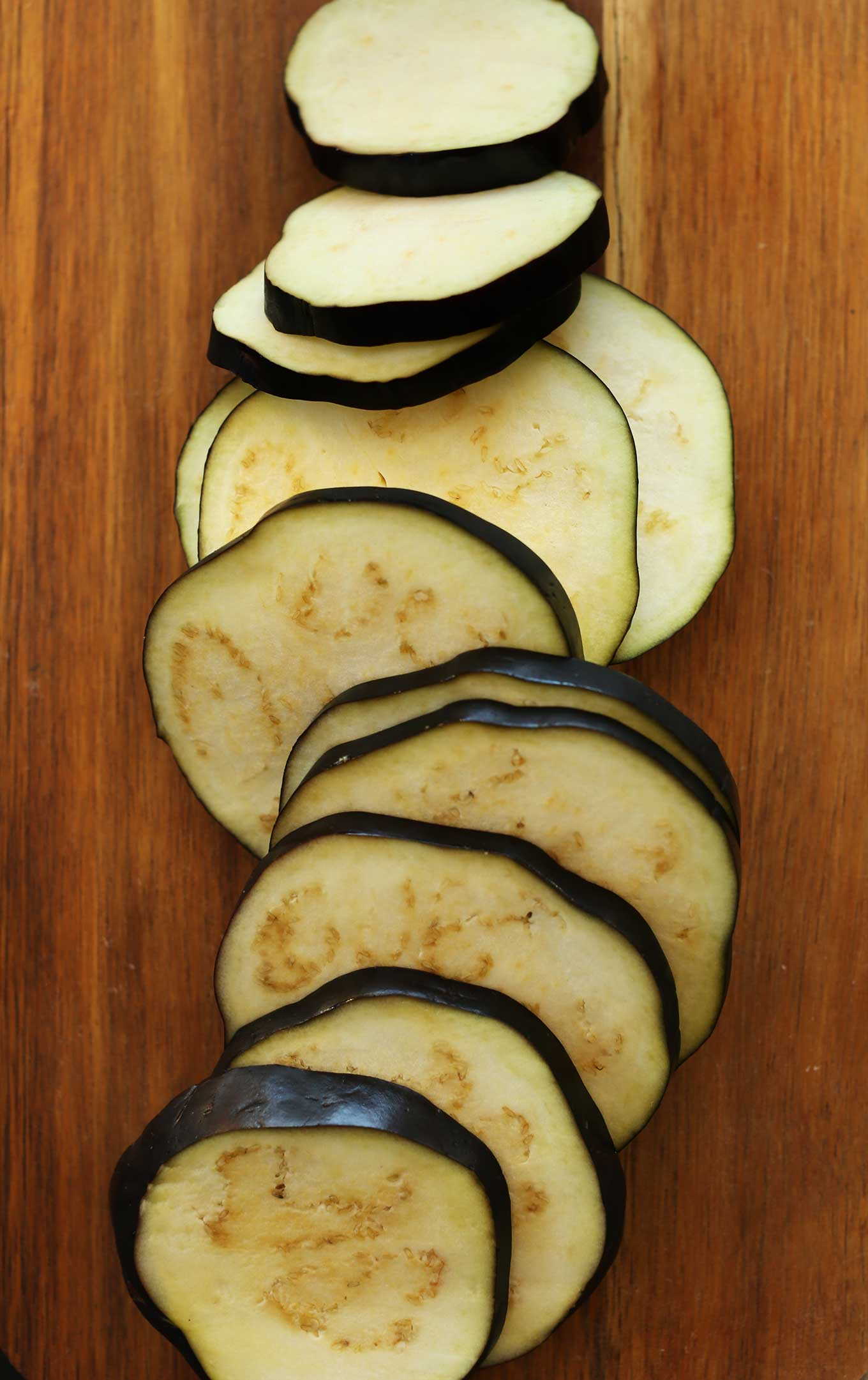 Thinly sliced eggplant on a cutting board