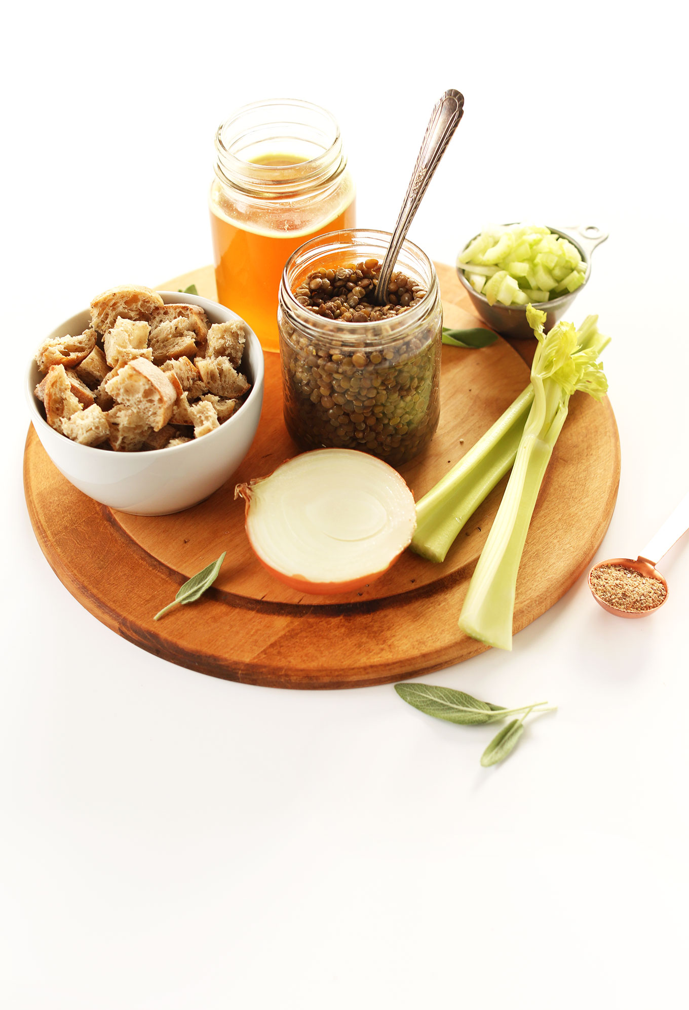 Cutting board with celery, onion, lentils, bread, and broth for making homemade vegan stuffing