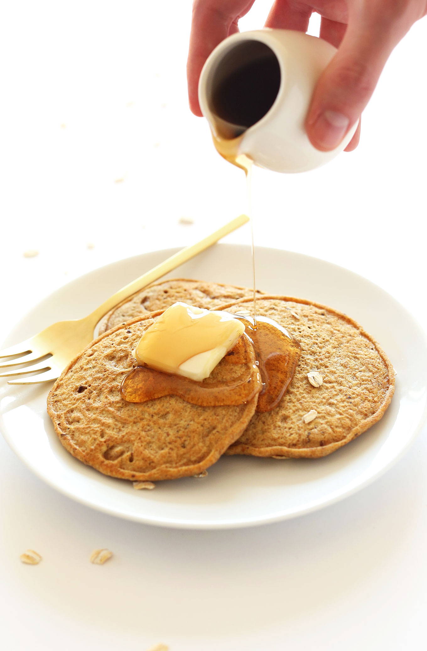 Pouring syrup onto Whole Grain Vegan Pancakes made with spelt flour