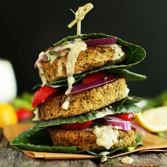 Stack of Baked Falafel Burgers with collard green leaves for a bun