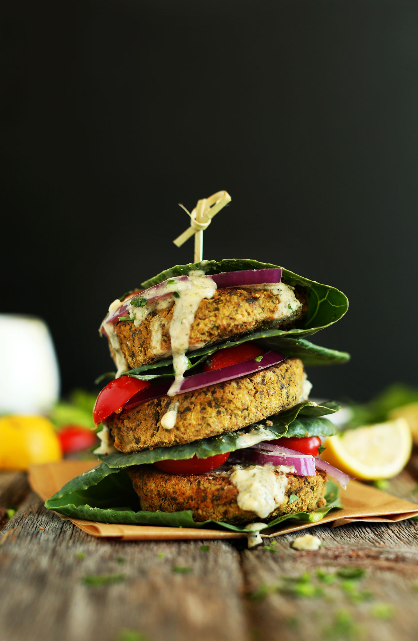 Stack of collard wrapped baked falafel burgers held together with a toothpick