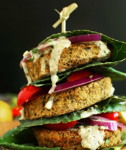 Stack of gluten-free vegan falafel burgers in collard wraps