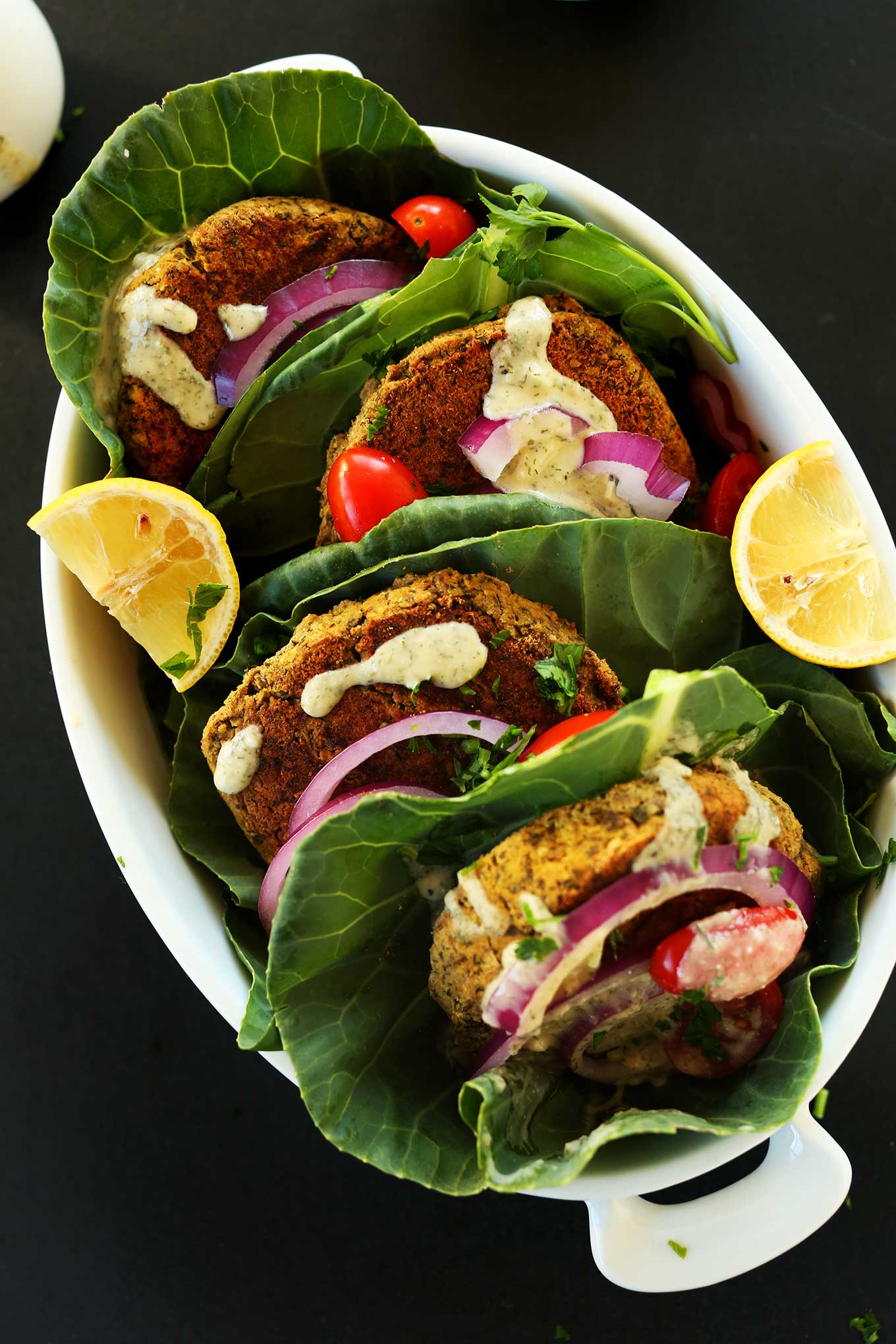 Large dish of falafel burgers wrapped in collard greens with onions, sauce, and other toppings