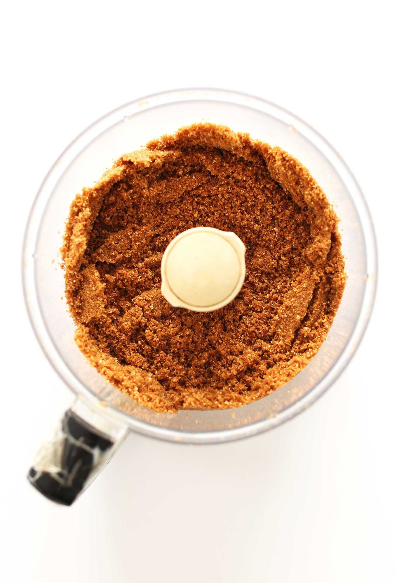 Food processor filled with crushed graham crackers for making cheesecake crust