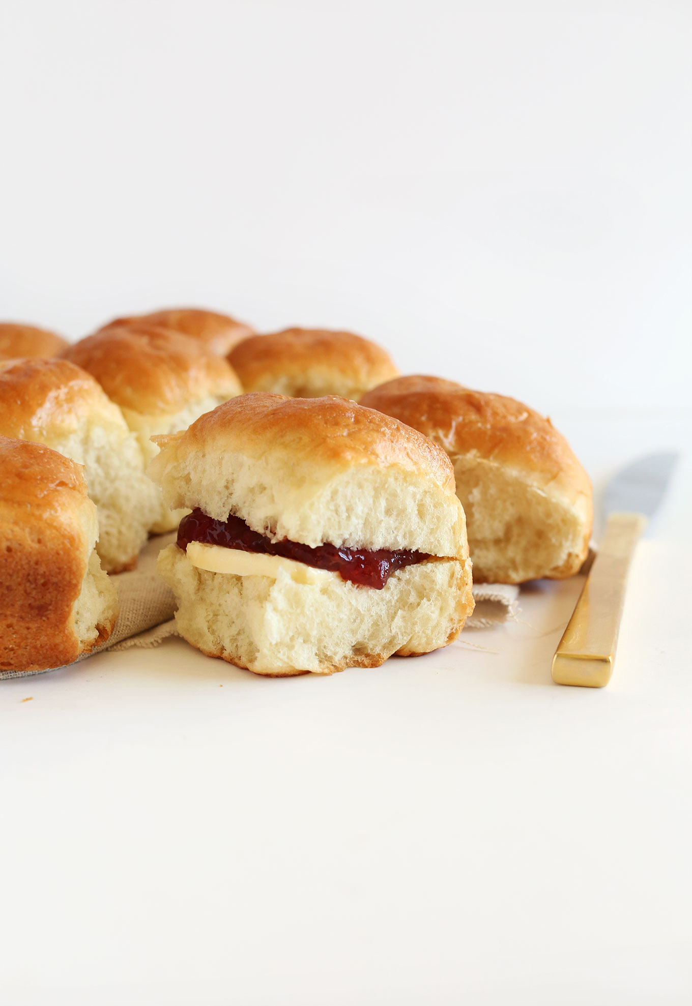 Freshly baked vegan dinner rolls filled with jam and vegan butter