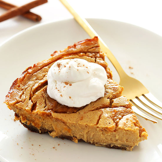 Plate with a slice of Vegan Pumpkin Swirl Cheesecake topped with coconut whipped cream