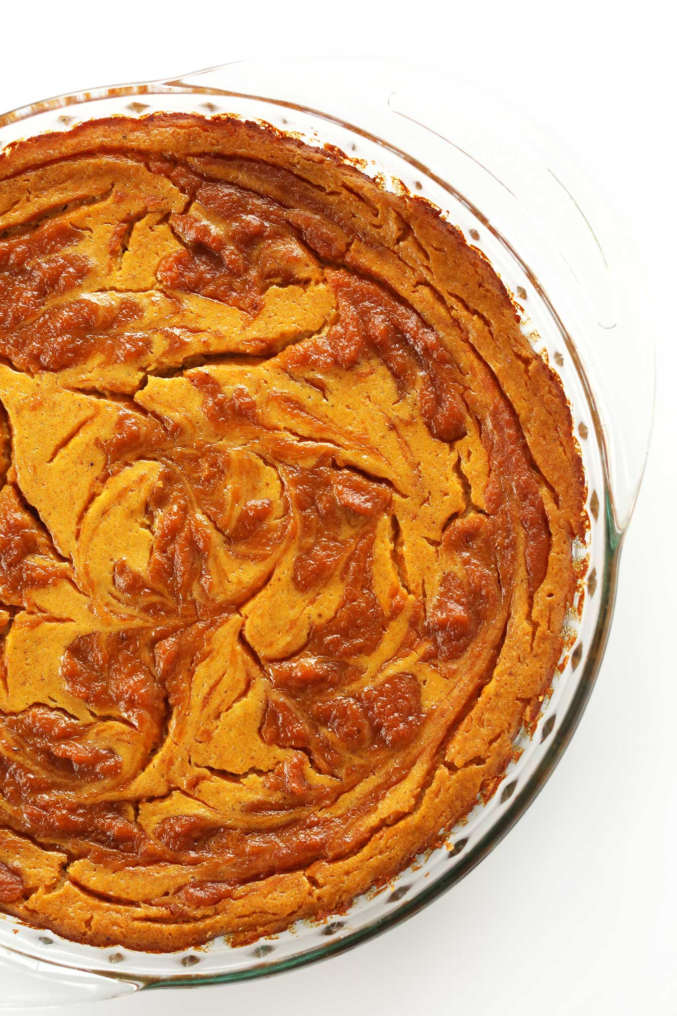 Freshly baked Vegan Pumpkin Swirl Cheesecake in a pie pan