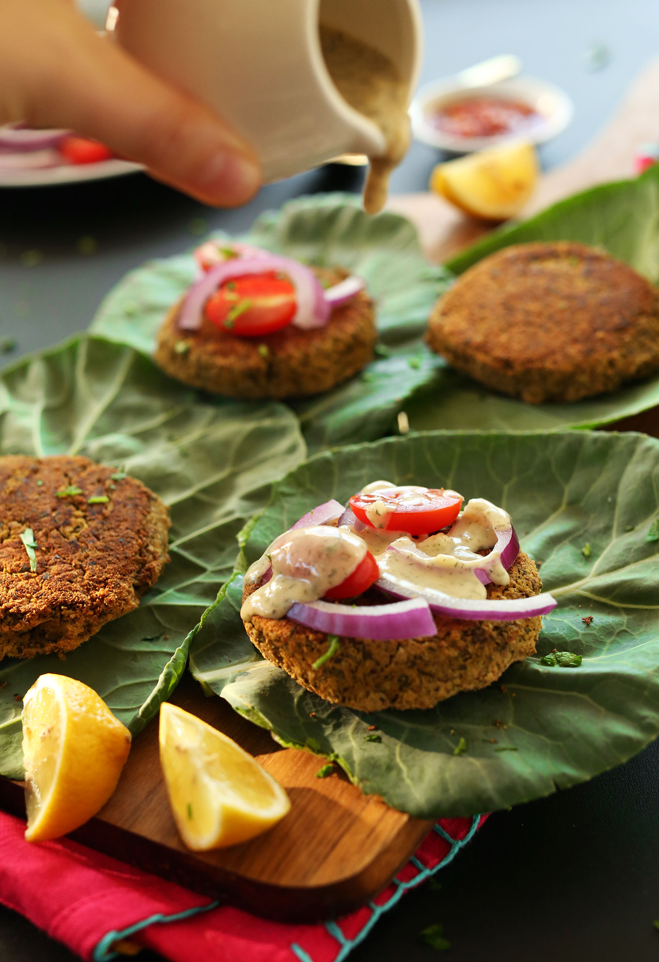 Pouring sauce over healthy baked falafel burgers