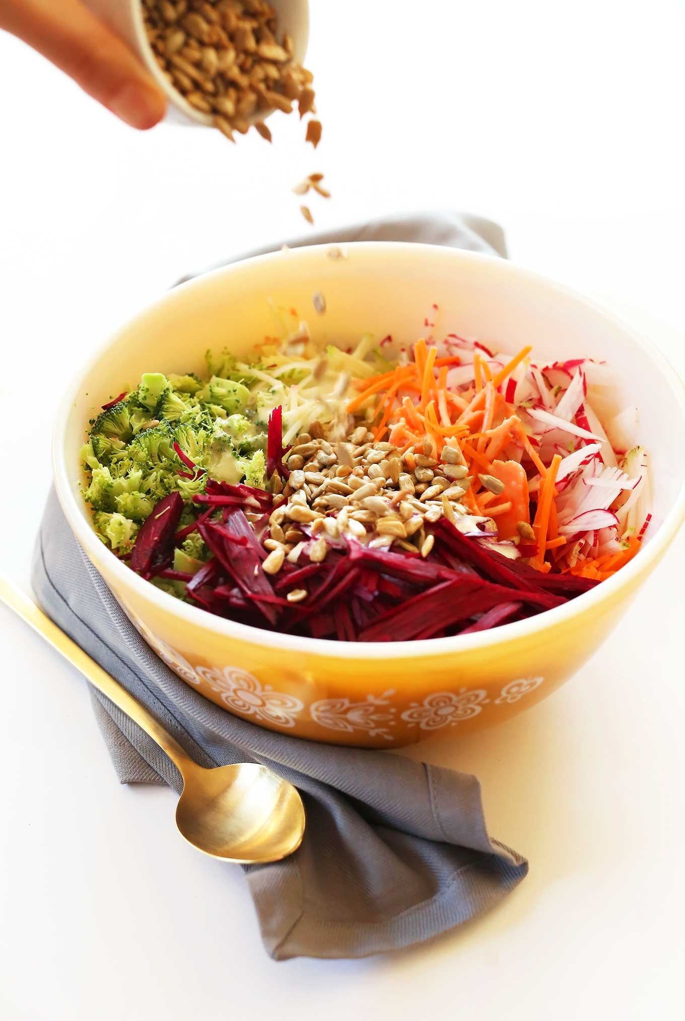 Sprinkling sunflower seeds onto our healthy fall slaw for a Thanksgiving salad