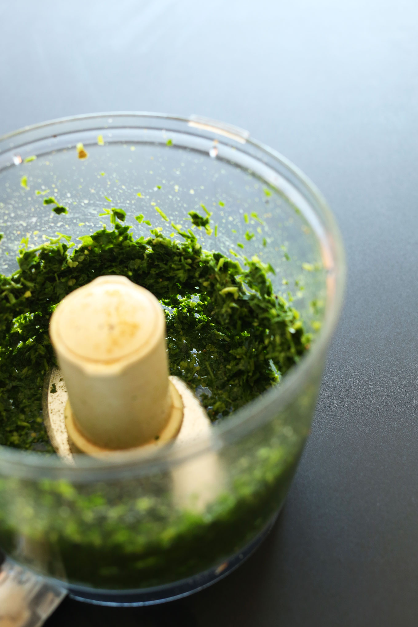 Pulsing green ingredients for falafel burgers in a food processor