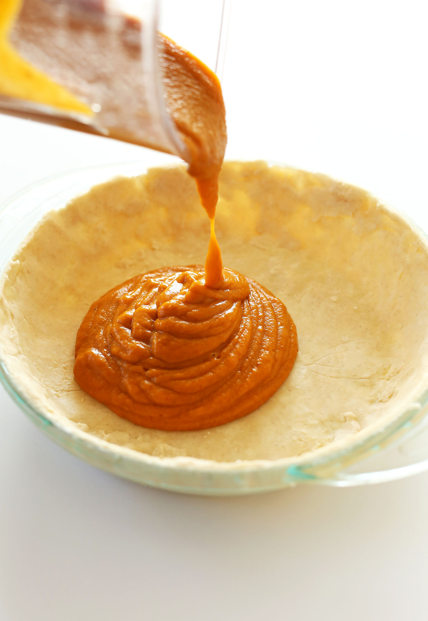 Pouring pumpkin filling into a gluten-free pie crust