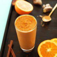Tall glass of our Immune Booster Orange Smoothie recipe on a baking sheet with ingredients to make it