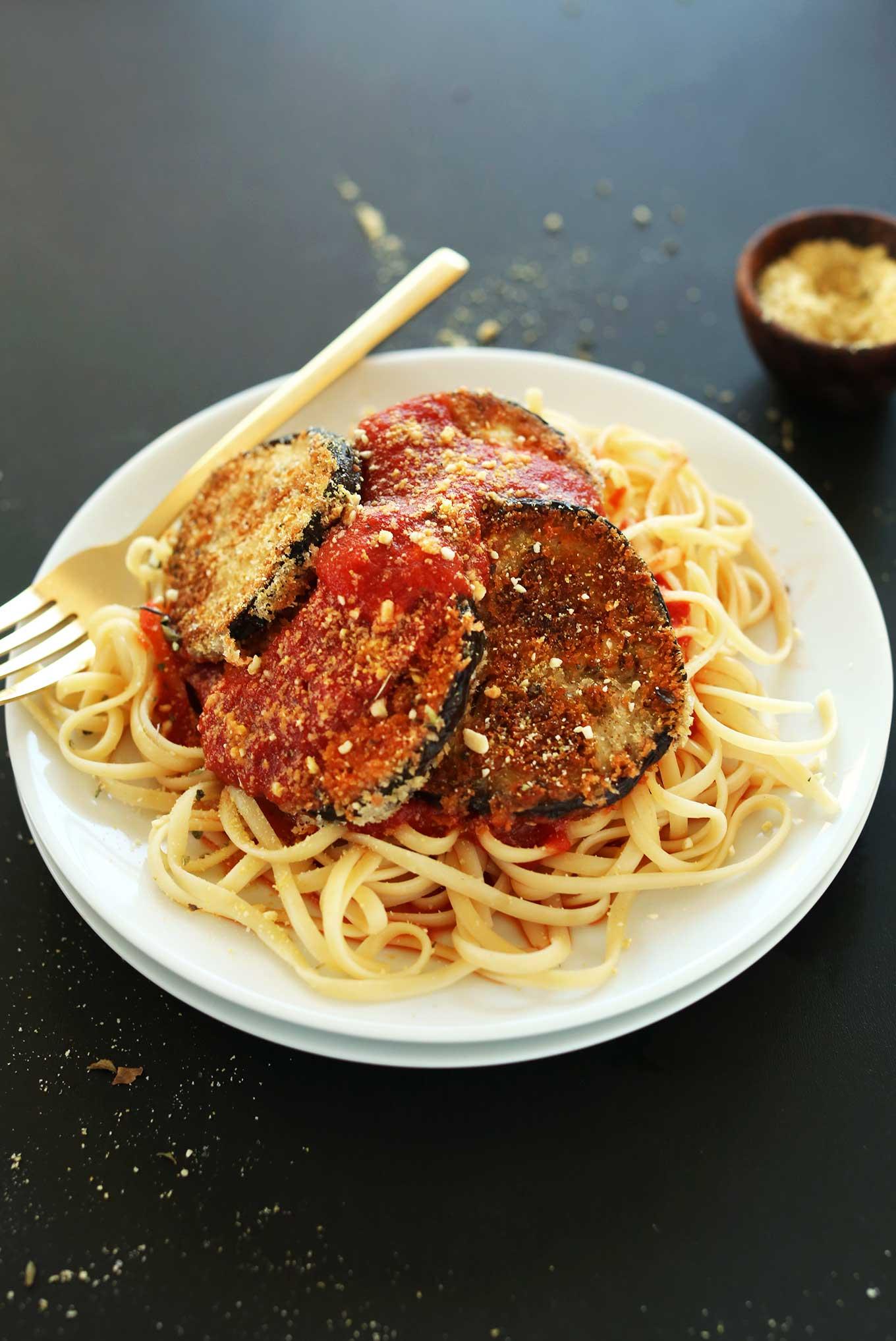 Plate loaded with noodles, marinara, and vegan eggplant parmesan