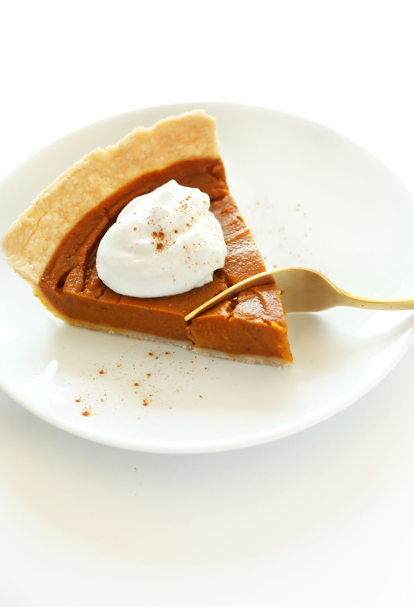 Grabbing a bite from the tip of a slice of vegan gluten-free pumpkin pie