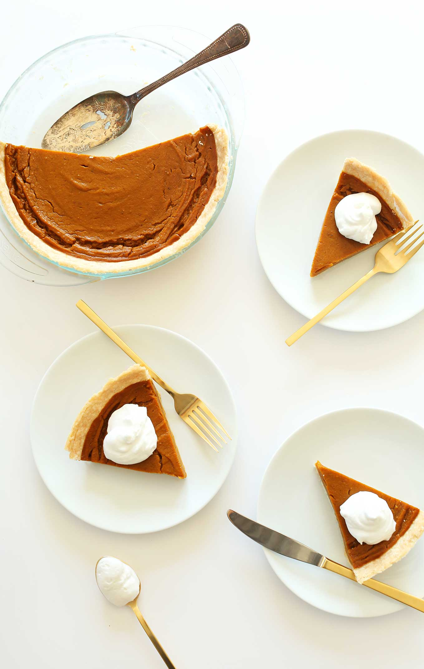 Plates with slices of Vegan Gluten-Free Pumpkin Pie and a pie pan with the rest