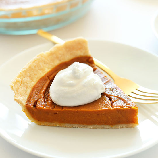 Slice of Vegan GF Pumpkin Pie topped with coconut whipped cream