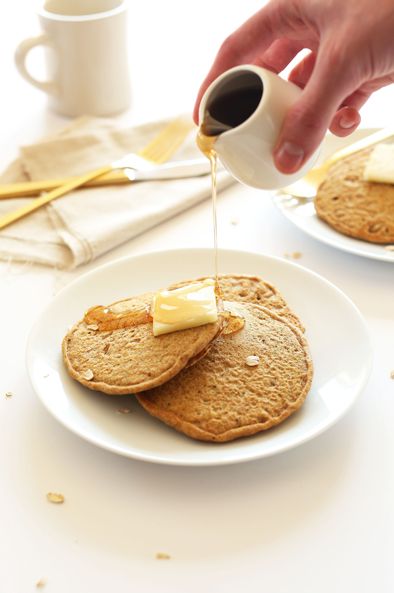 Pouring syrup onto a plate of simple Whole Grain, Healthy Vegan Pancakes