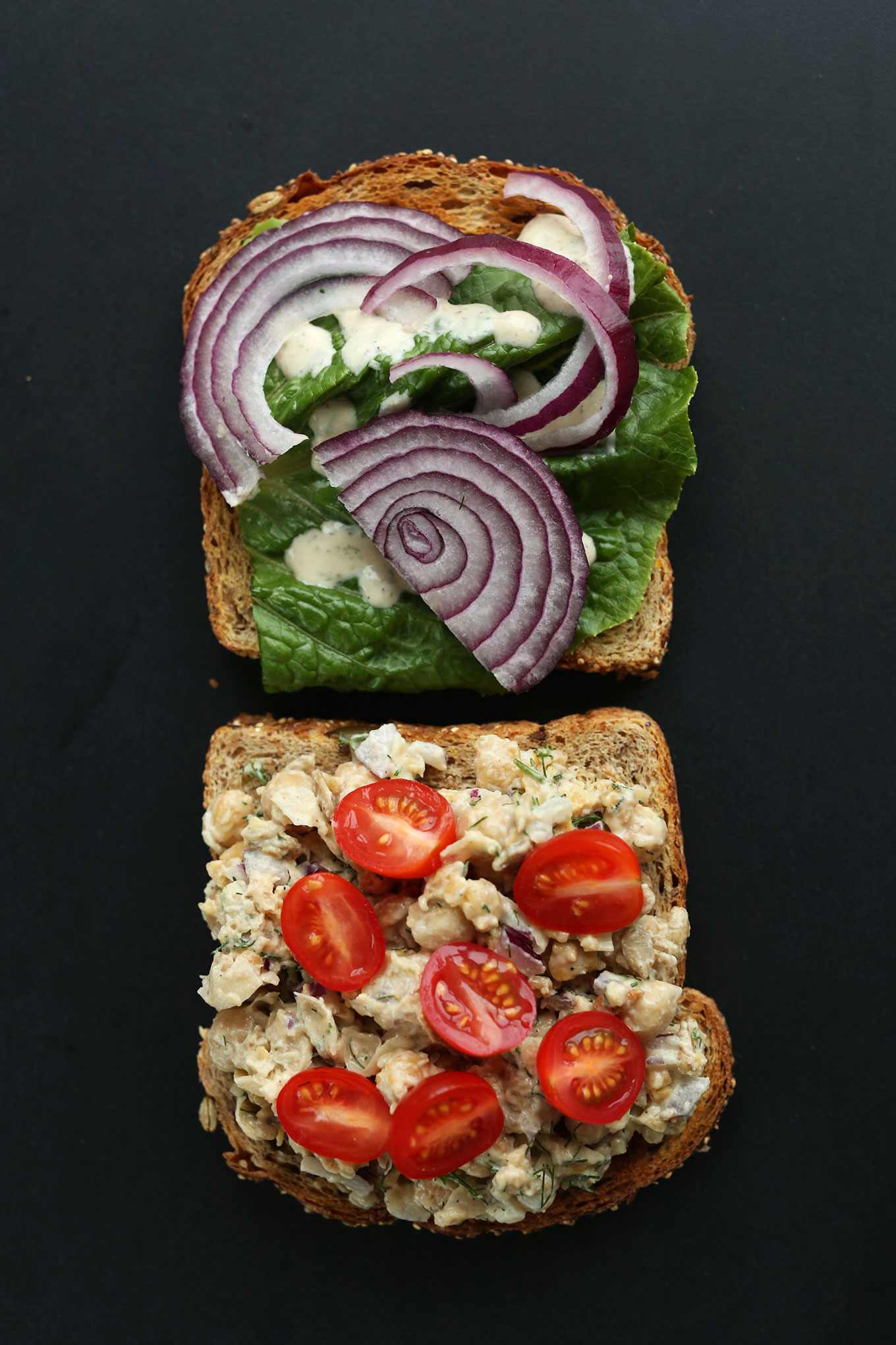 Slices of bread with lettuce, red onion, tomatoes, and Chickpea Sunflower Salad
