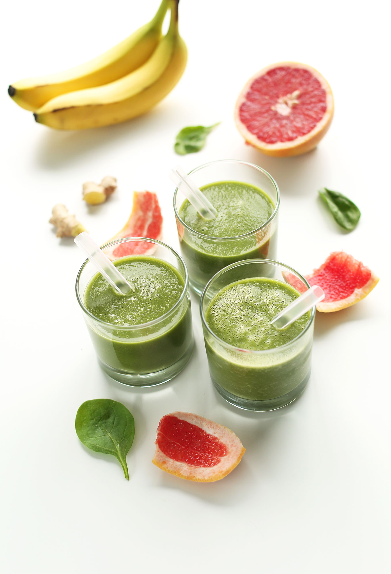 Glasses of our gluten-free vegan Grapefruit Green Smoothie surrounded by ingredients used to make the recipe