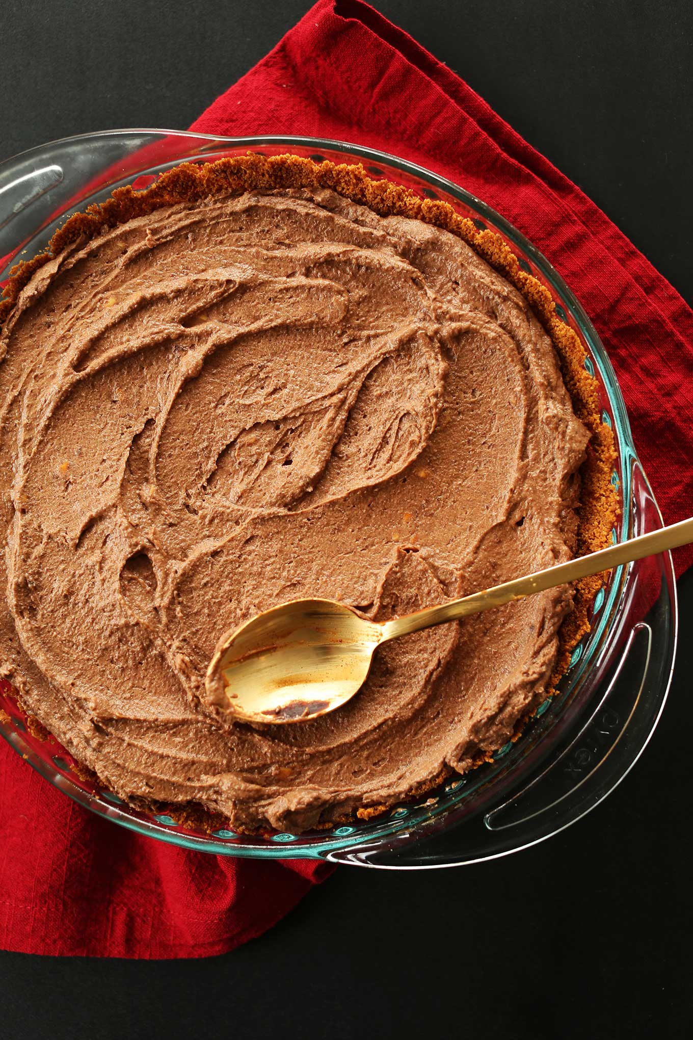 Spreading Vegan Chocolate Peanut Butter Mousse into a pie pan for a delicious vegan dessert