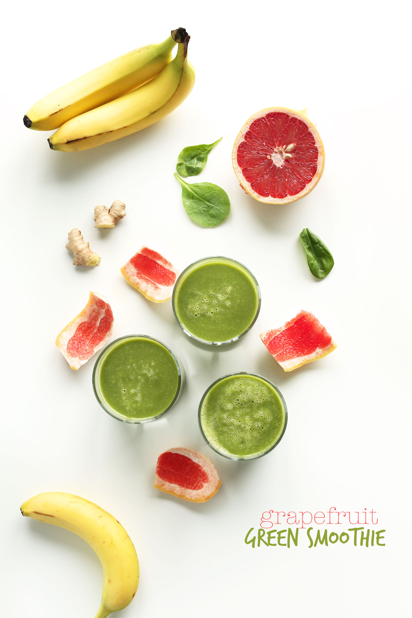 Grapefruit Green Smoothies surrounded by ginger, spinach, bananas, and grapefruit