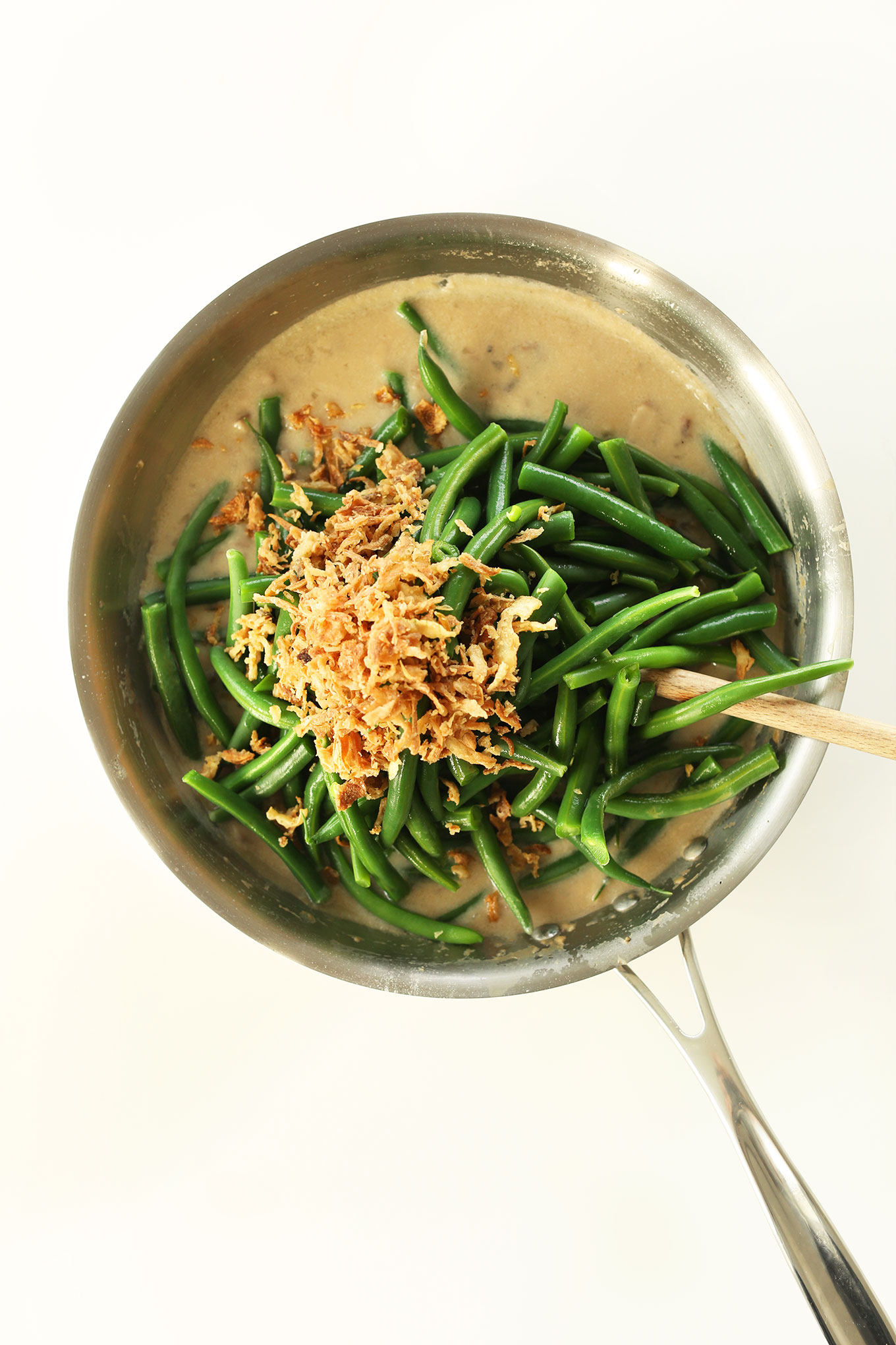 Using a wooden spoon to stir together our Easy Green Bean Casserole recipe