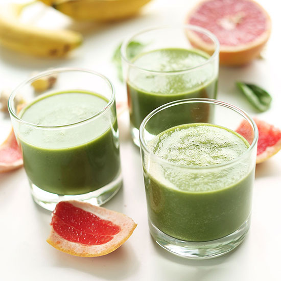 Three glasses of our Grapefruit Green Smoothie surrounded by ingredients used to make it