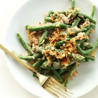 Plate of Creamy Vegan Green Bean Casserole topped with crispy onions
