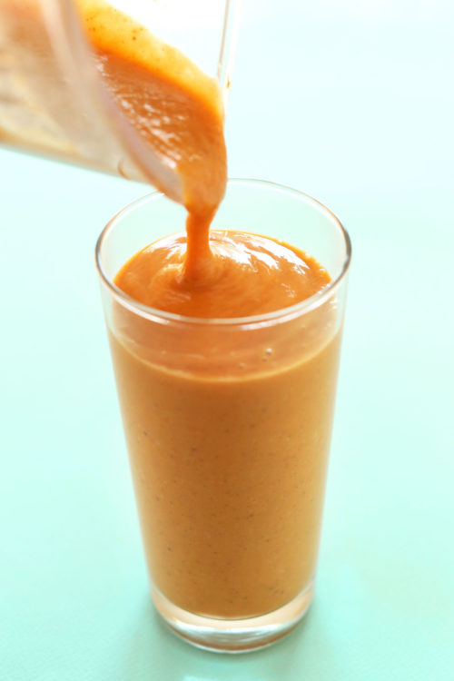 Pouring a tall glass of our vibrant Orange Sweet Potato Smoothie