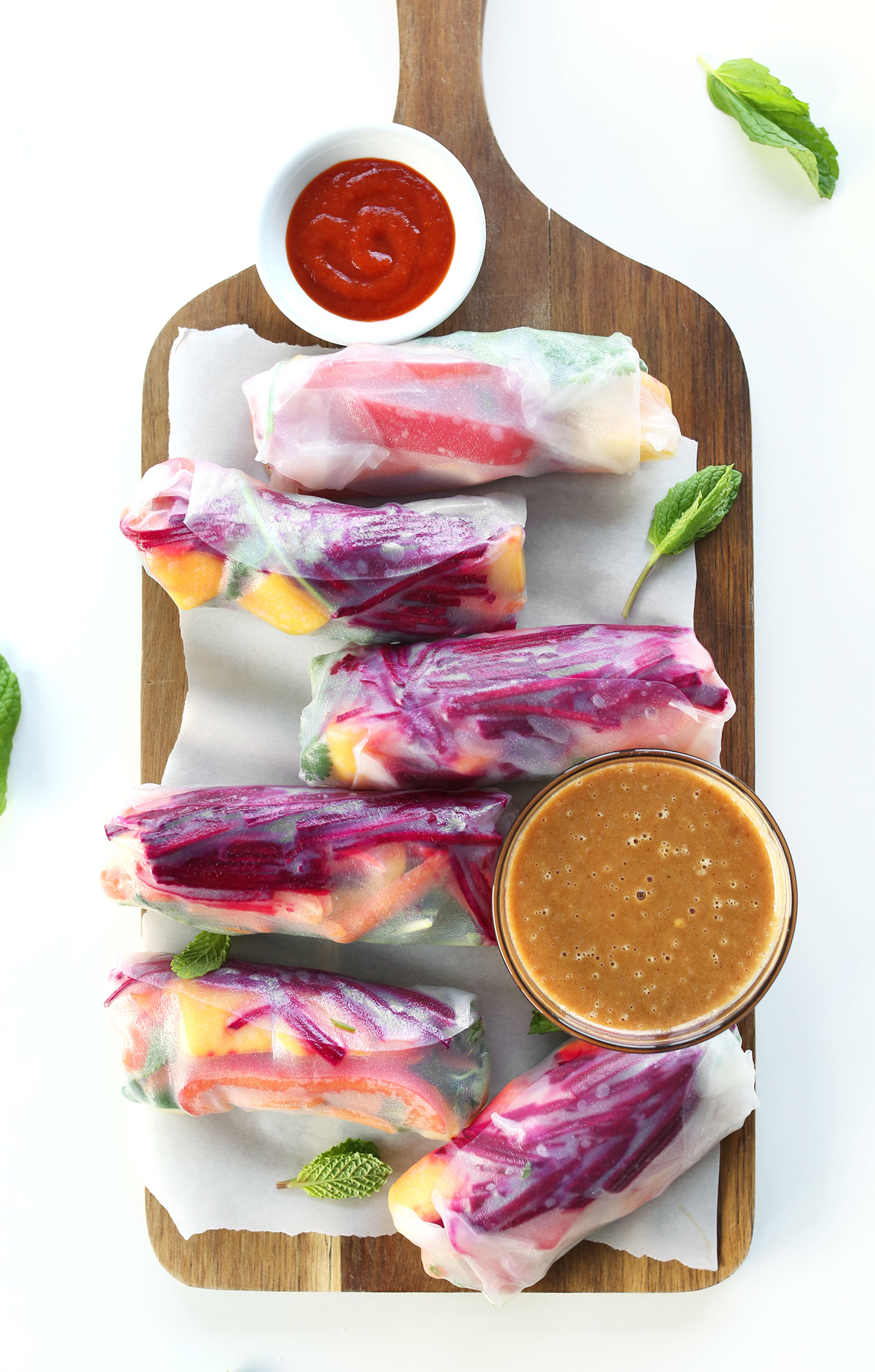 Wood platter filled with vegan Rainbow Spring Rolls and Peanut Sauce