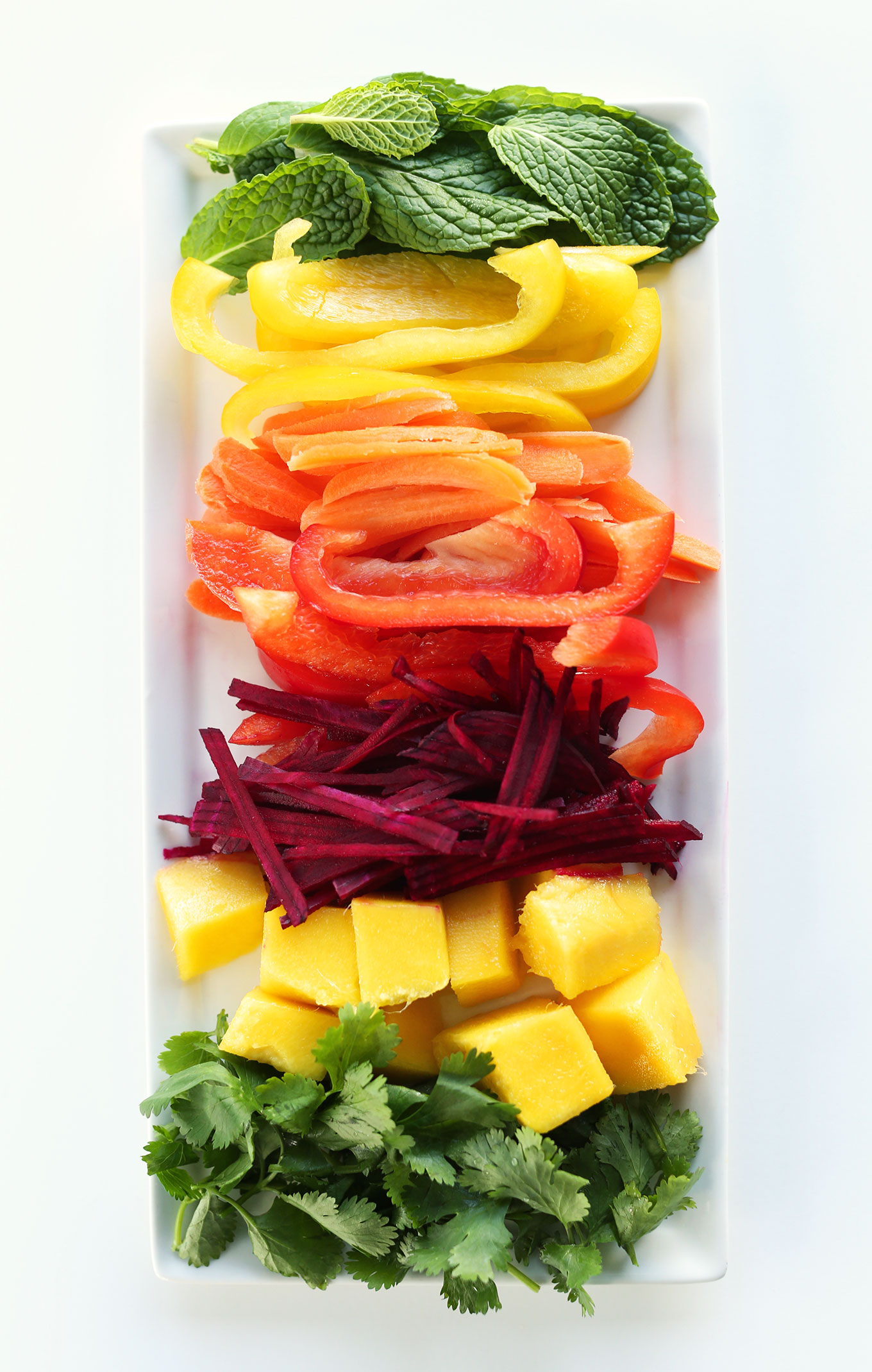 Freshly sliced vegetables and mango for making Rainbow Spring Rolls