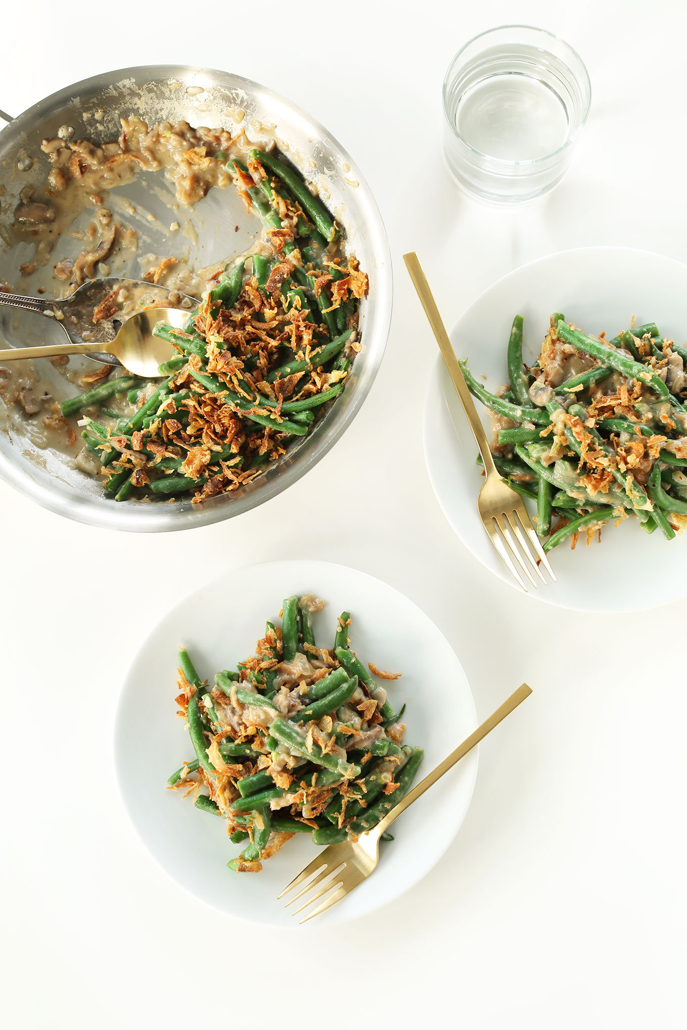 Using a spoon to scoop Vegan Green Bean Casserole onto serving plates