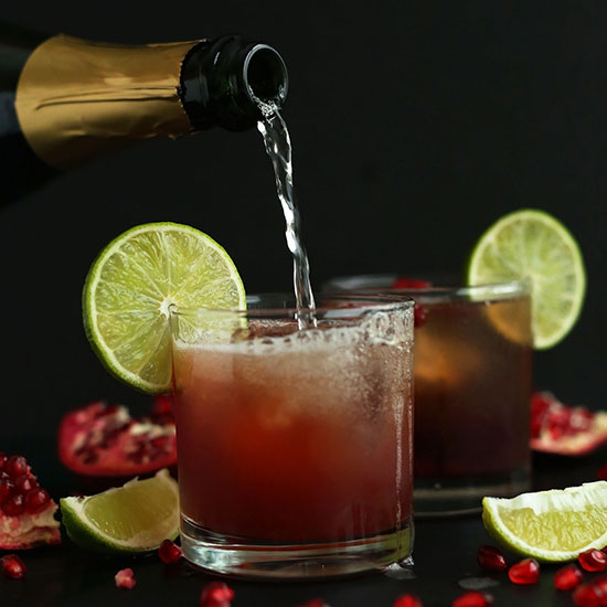 Pouring sparkling wine into a glass to make a Sparkling Pomegranate Margarita