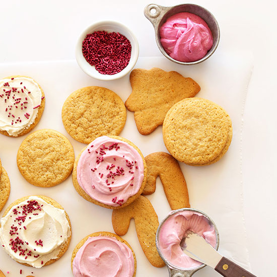 Assorted shapes of Vegan Sugar Cookies with pink and white frosting and sprinkles