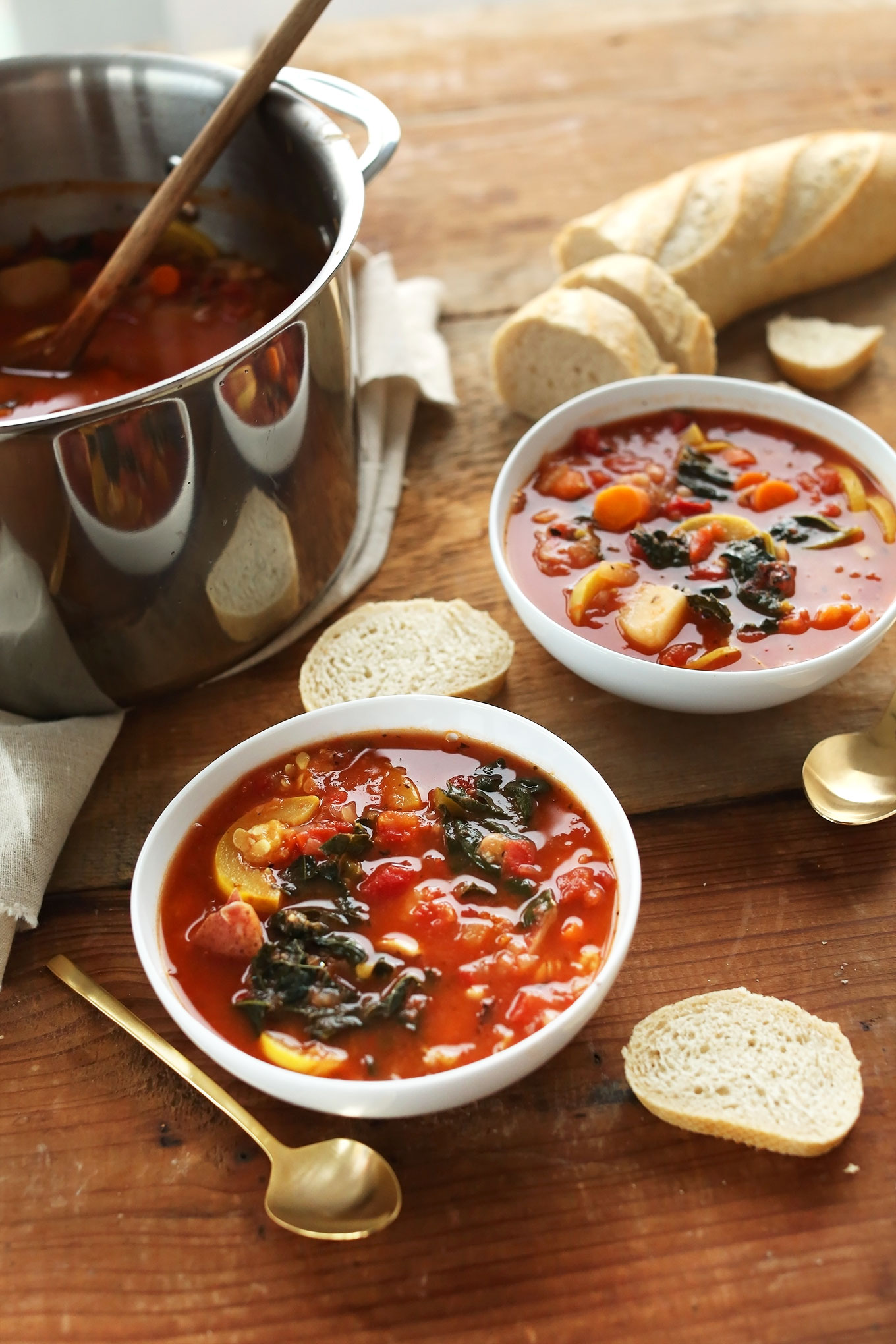Bowls of our 1-Pot Veggie and White Bean Stew with slices of bread