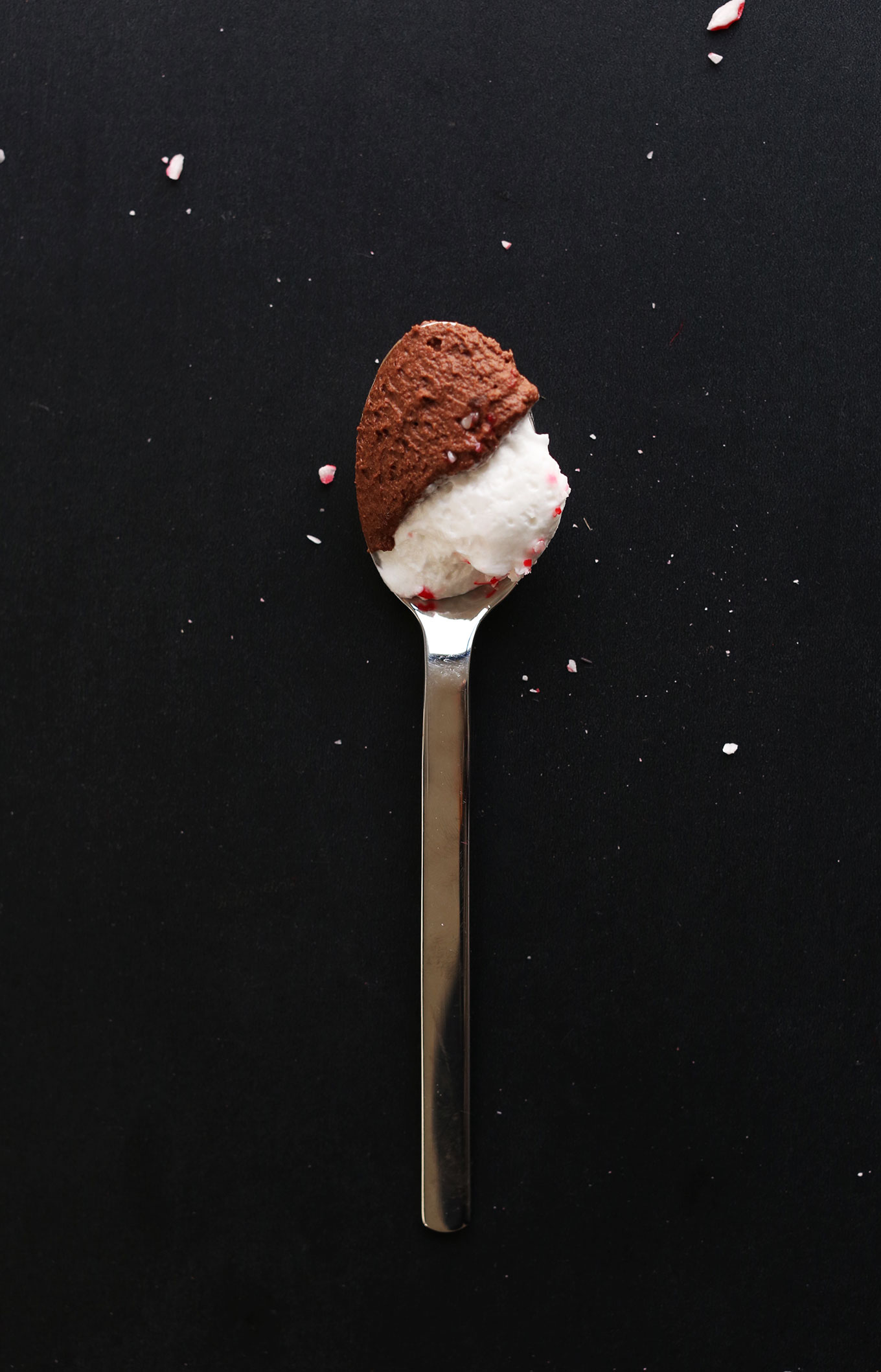 Spoonful of homemade Dark Chocolate Peppermint Mousse topped with coconut whipped cream