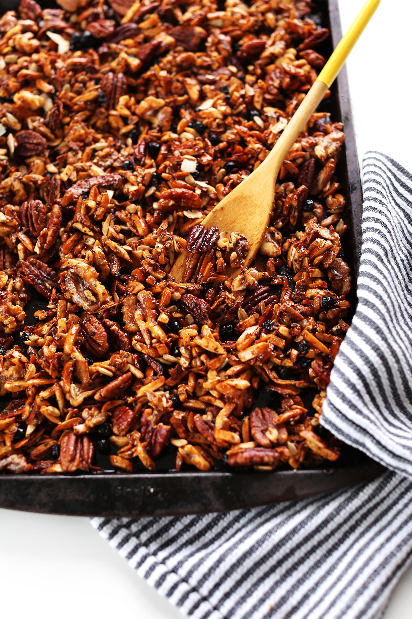 Using a wooden spoon to stir our Grain-Free Granola on a baking sheet