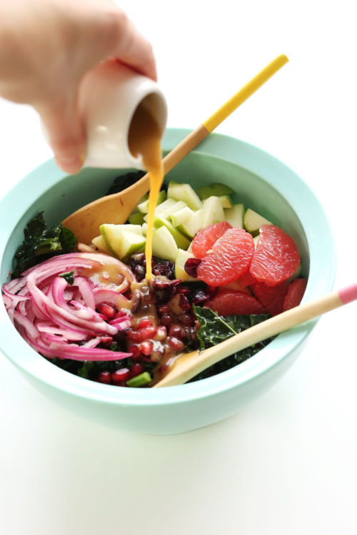 Drizzling homemade red wine vinaigrette onto a big bowl of our Citrus Kale Salad recipe