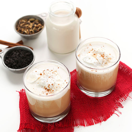 Dairy-free milk, spices, and two glasses of our homemade Vegan Chai Latte recipe