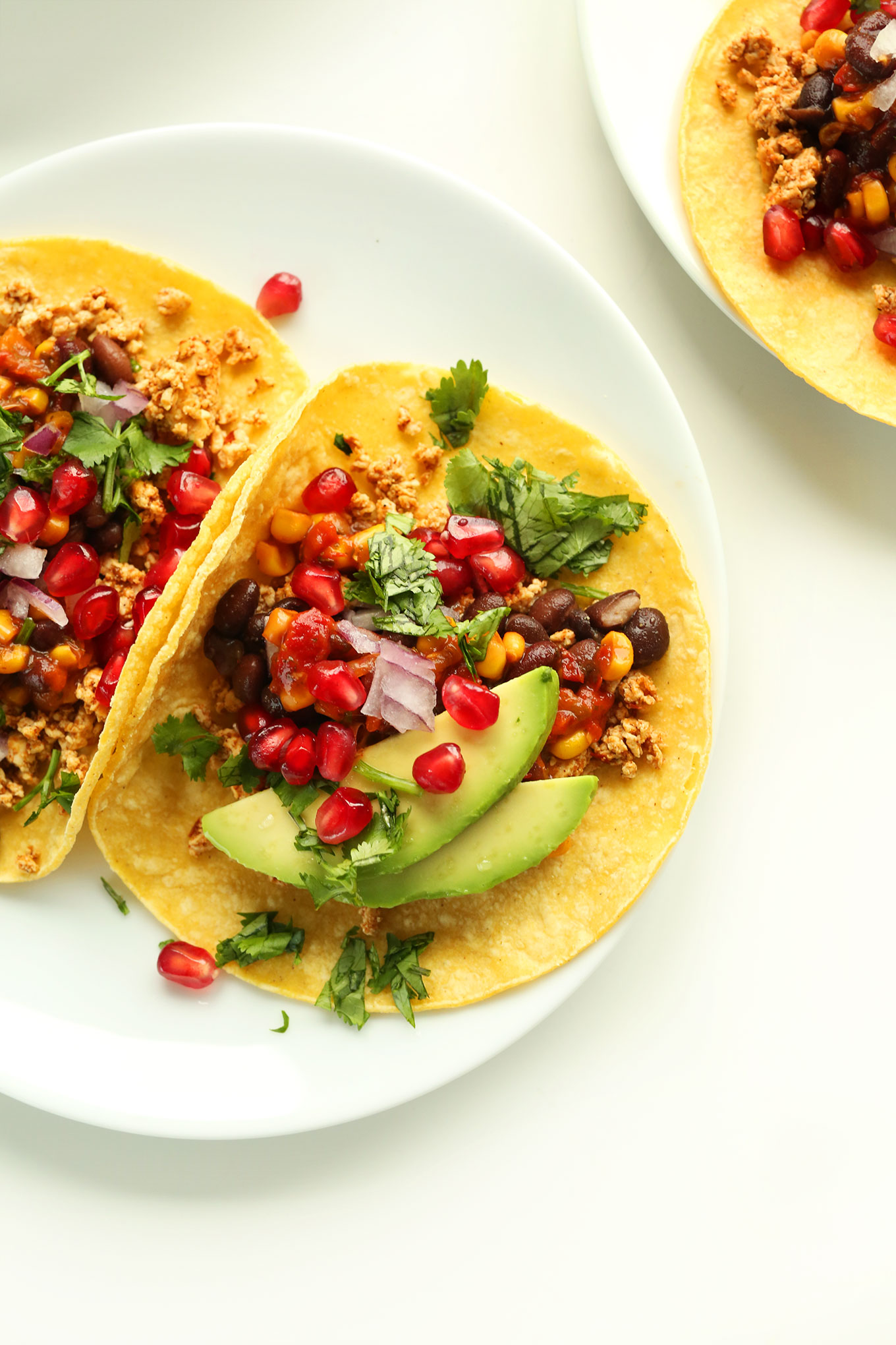 Close up shot of vegan breakfast tacos made with spicy tofu, black beans, fruit, and veggies