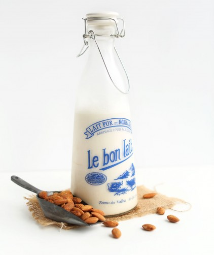 Jug of fresh homemade almond milk alongside a scoop of raw almonds