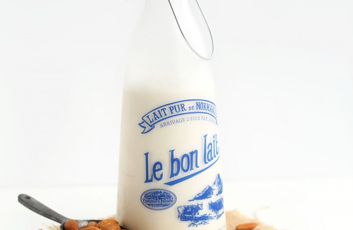 Jug of homemade almond milk and a scoop of raw almonds for our How to Make Almond Milk tutorial