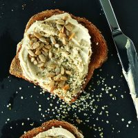 Slices of toast topped with hummus, sunflower seeds, and hemp seeds