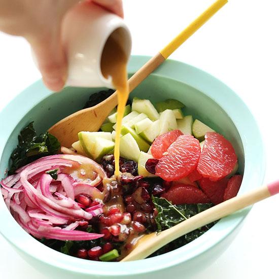 Pouring Red Wine Vinaigrette onto a big bowl of Kale Citrus Salad